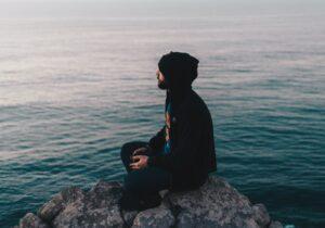 man sitting on rock near ocean water